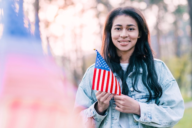 Beautiful woman with souvenir american flag outdoors