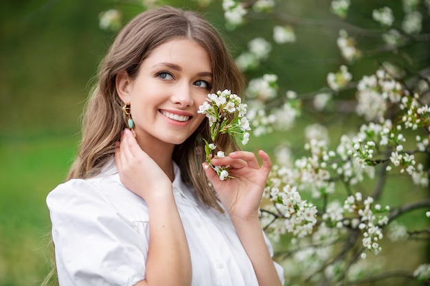 Beautiful woman with spring blooming flowers on a tree.