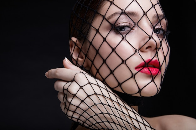 Beautiful woman with stocking mesh on her face in studio on gray background bright makeup red lips
