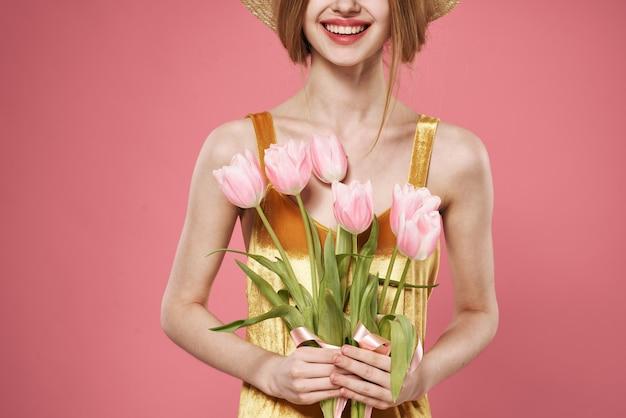 花の花束を保持している麦わら帽子を持つ美しい女性