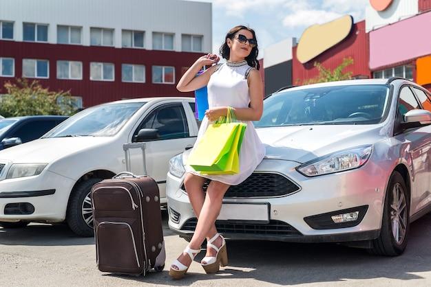 Красивая женщина с чемоданом и хозяйственными сумками возле автомобиля