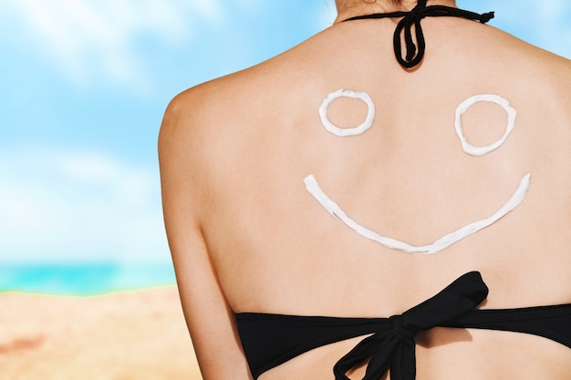 Beautiful woman with sunscreen solar cream over ocean background. sun tanning.