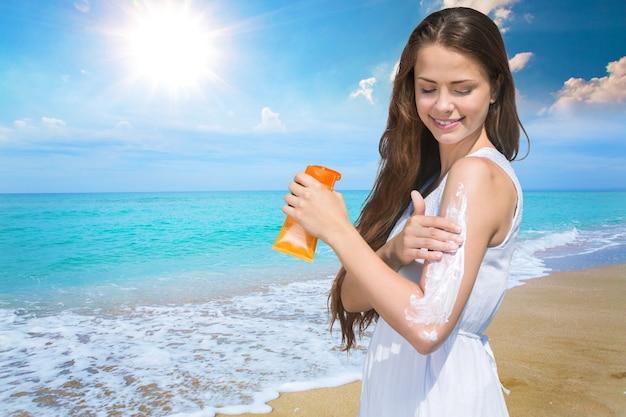 海の背景に日焼け止めソーラークリームと美しい女性。日焼け。