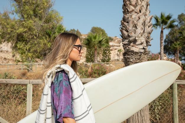Красивая женщина с доской для серфинга на пляже