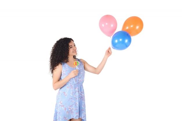 甘いロリポップと風船を持つ美しい女性。