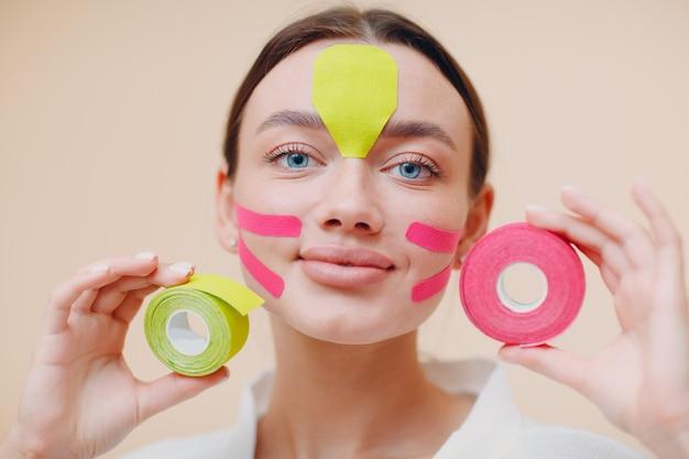 フェイスリフティング治療手順の顔の構築の概念のための手にテープを持つ美しい女性