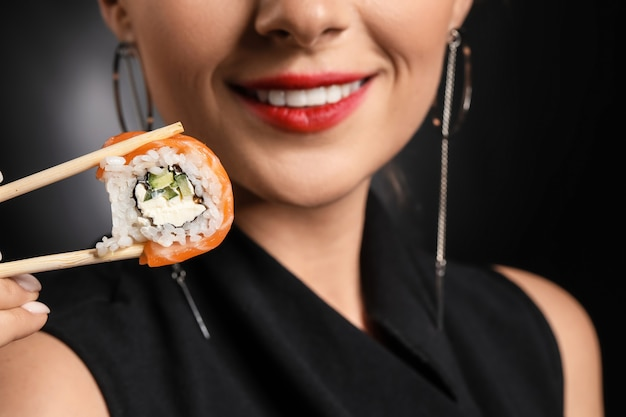 Beautiful woman with tasty sushi on dark background, closeup