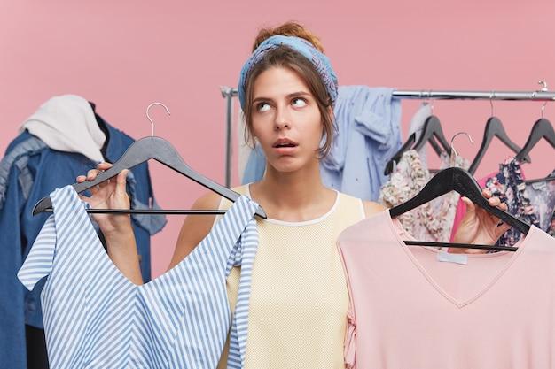 2つの間を選択するドレスで2つのハンガーを保持している疲れた表情の美しい女性。ブティックで服を提供する不満の若い女性の売り手、気難しいクライアントに疲れきっています