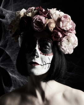 Beautiful woman with traditional mexican death mask. calavera catrina. sugar skull makeup. woman dressed in a wreath of roses