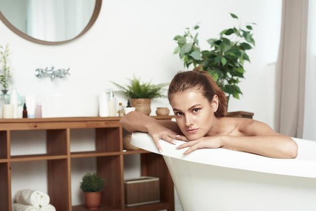 白斑を持つ美しい女性がカメラに微笑んで、お風呂に横たわっています。閉じる。