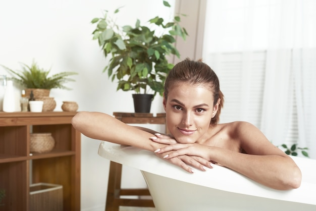 白斑を持つ美しい女性はお風呂に横たわって、笑顔で、リラックスします。バスルームでのリラクゼーションコンセプト。