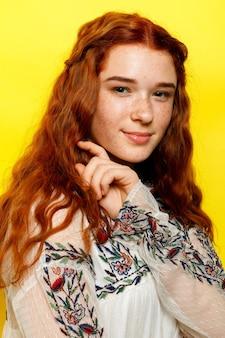 Красивая женщина с волнистыми рыжими волосами на желтом фоне