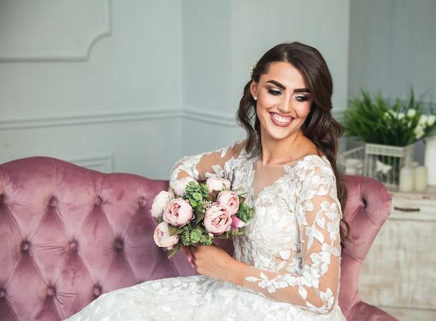 長い巻き毛の結婚式のメイク、ドレス、ジュエリーリースと美しい女性。魅力的な若い花嫁の肖像画。インテリアでポーズをとるブライダルファッションモデル。官能的な女性。髪型、美容、花