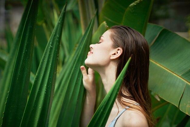 자연 덤불 모델 정글에 녹색 잎 근처에 젖은 머리를 가진 아름 다운 여자