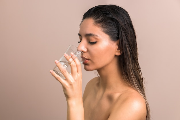 Beautiful woman with wet hairs and bare shoulders drinking water from glass. skin care body hydration