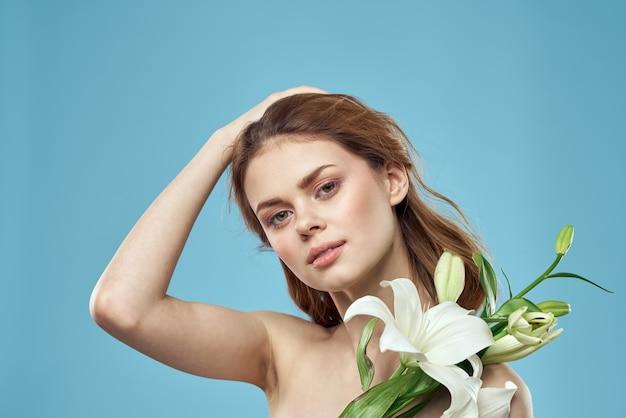 青い背景の上の彼女の手に白い花を持つ美しい女性