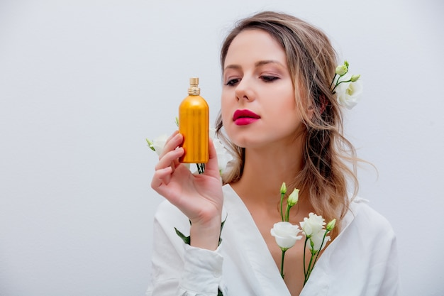 Beautiful woman with white roses dressing in a white shirt holding a golden perfume bottle. springtime concept or valentines day holiday