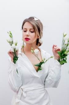 Beautiful woman with white roses in sleeve, dressing in a white dress. springtime concept or valentines day holiday
