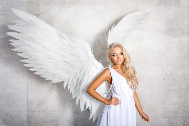 Beautiful woman with white wings on white background