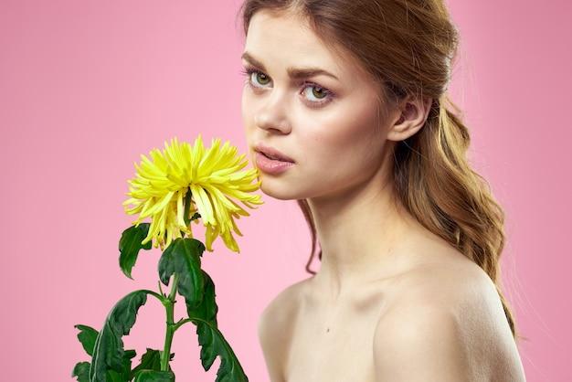 ピンクの背景に黄色い花を手に美しい女性