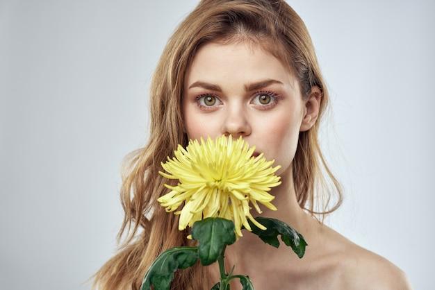 白い背景の上の彼女の手に黄色い花を持つ美しい女性
