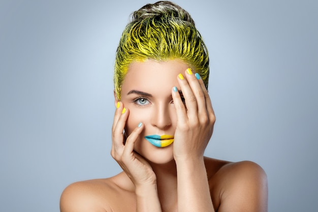 Beautiful woman with yellow hair and colorful nails and lips