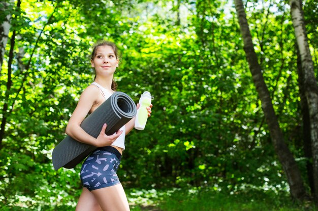 Beautiful woman with a yoga mat outdoors.