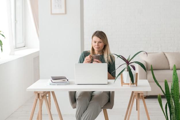 Красивая женщина работает в современной студии, пьет кофе и смотрит на экран компьютера, ноутбук, видеочат или видеоконференцию, бизнес онлайн