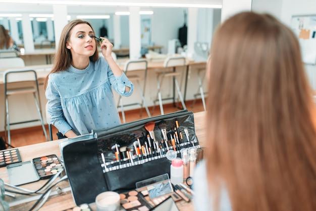 Красивая женщина работает с собственным лицом против зеркала в студии красоты.