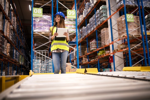 ヘルメットと倉庫センターでの流通を制御するチェックリストを持つ美しい女性労働者