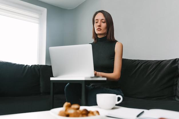 ソファに座ってノートパソコンの後ろで自宅で働く美しい女性