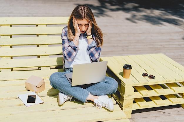 Красивая женщина, работающая за ноутбуком, садится на скамейку снаружи и пьет кофе с помощью компьютера и