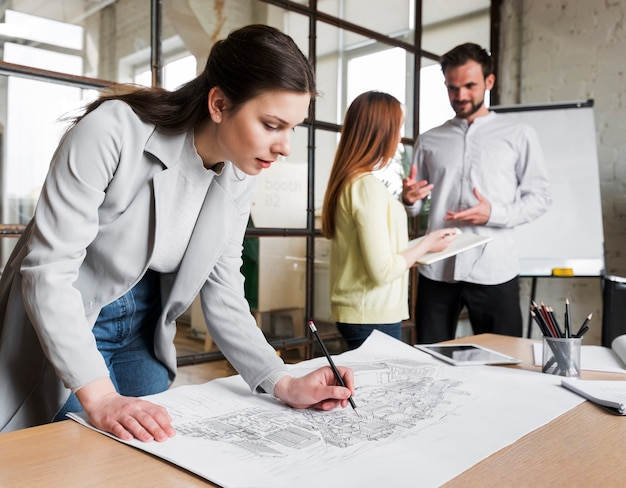 Beautiful woman working on blue print while her colleague discussing something on background