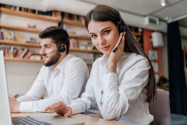Beautiful woman working in call center with headset and man