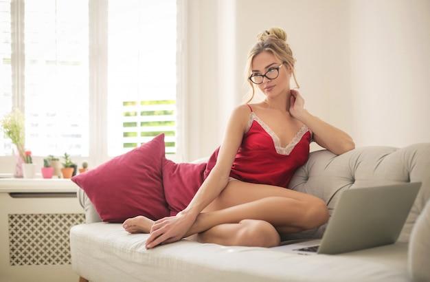 Красивая женщина работает из дома с ее ноутбуком
