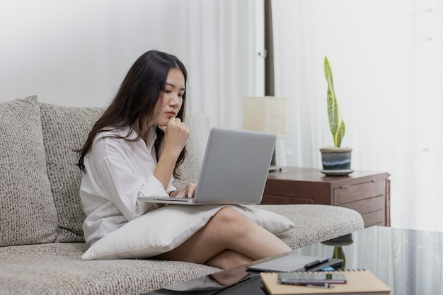 A beautiful woman working at home with a laptop and tablet computer.