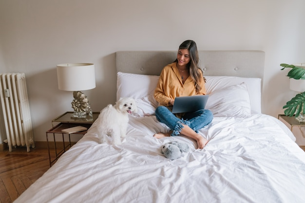 Beautiful woman working on laptop at home. cute small dog besides