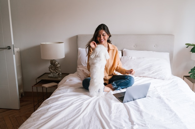 Beautiful woman working on laptop at home with her dog