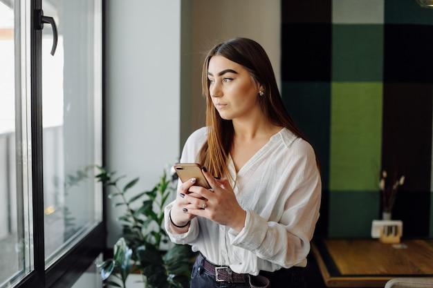 세련된 도시 레스토랑에서 그녀의 노트북과 휴대 전화에서 작업하는 아름 다운 여자