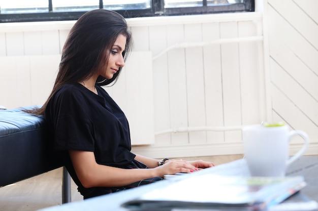 Красивая женщина, работающая на своем ноутбуке