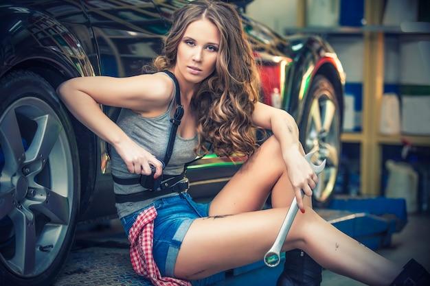 쇼룸에서 차를 수리하기 위해 노력하는 아름 다운 여자