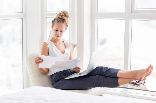 Красивая женщина, работающая с документами на лоджию