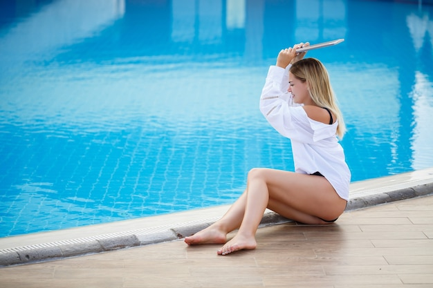 Beautiful woman working with laptop by the pool. freelance remote work