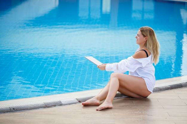 Красивая женщина, работающая с ноутбуком у бассейна. удаленная работа фрилансером