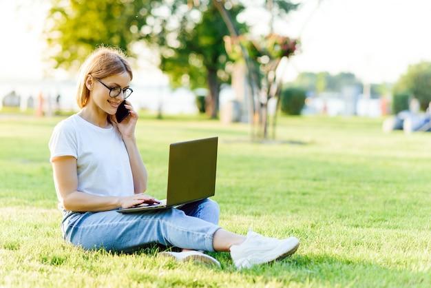 芝生の上の公園でノートパソコンで作業している美しい女性。リモートワークの概念