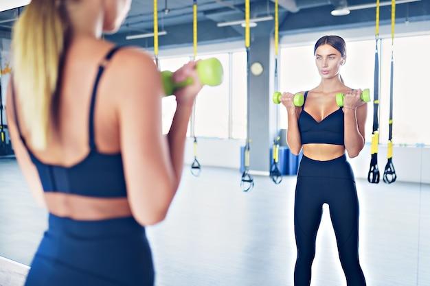 鏡、ジムの前でダンベルと美しい女性のトレーニング。