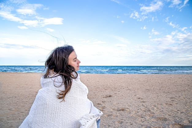 담요에 싸여 아름 다운 여자는 해변에서 거리에 보인다.