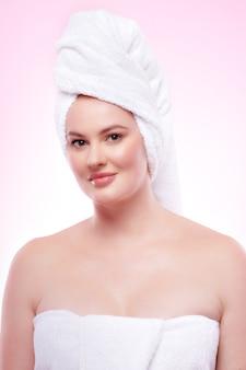 분홍색 배경에서 스파 트리트먼트를 받은 후 수건에 싸인 아름다운 여성