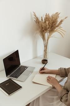 ノートシートに書いている美しい女性。快適なホームオフィスワークスペースのインテリアデザイン