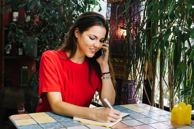 Beautiful woman writing schedul in diary while talking on cellphone